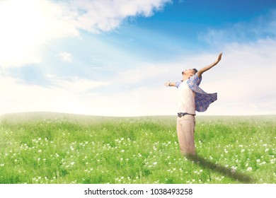 Happy man with arms wide open enjoying spring on blossom meadow. Summer or Spring concept