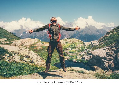 Happy Man with backpack jumping hands raised mountains landscape on background Lifestyle Travel happy emotions concept active summer vacations outdoor