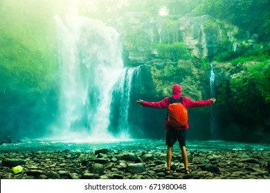 Happy man backpacker enjoying amazing tropical waterfall raised hands Travel Lifestyle and success concept vacations into the wild nature on background mountain