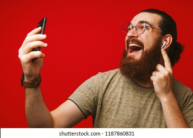 Happy man with beard listening music at airpods over red background