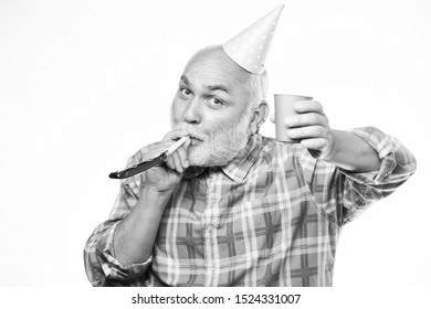 happy man with beard. retirement party. man hold party cone hat and whistle. happy birthday. corporate party. anniversary holiday celebration. mature bearded man in pionted hat. Multi colored fun.