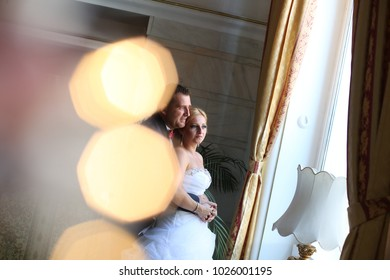 Happy man and beautiful woman in a wedding dress standing near the window