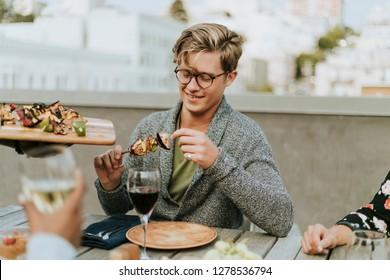 Happy man being served with vegan barbeque skewers