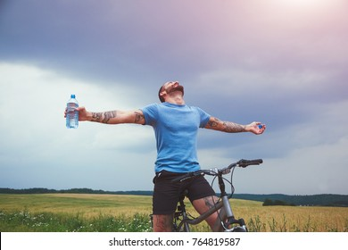 Happy man with bike spreading hands and drinking water resting. Freedom or happiness concept
