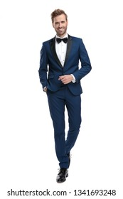 happy man in blue tuxedo walking with hand in pocket on white background