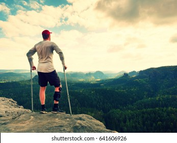Happy man with broken leg in immobilizer and medicine pole stay on  the peak. Open mountain valley bellow cliff. Tired tourist with crutches in  hands. Spring weather