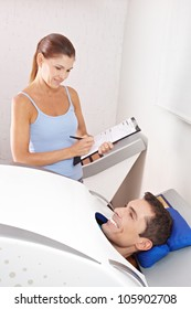 Happy man in cabin ozone for skin treatment with fitness trainer in spa