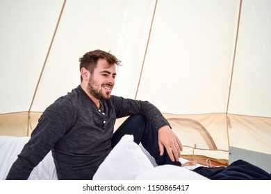 Happy man camping in a glamping tent in Iceland