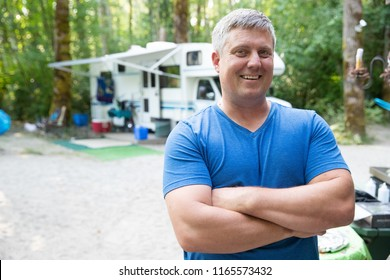 Happy man camping outside with an RV