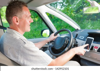 Happy man in the car using his mobile as a navigation GPS or receiving call