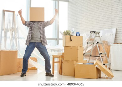 Happy man with cardboard box on his head showing thumbs-up