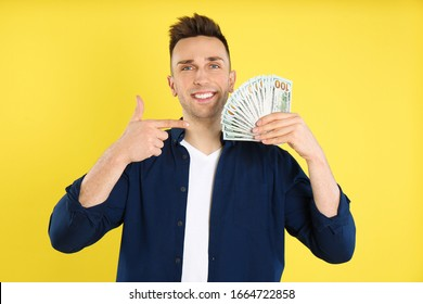 Happy man with cash money on yellow background