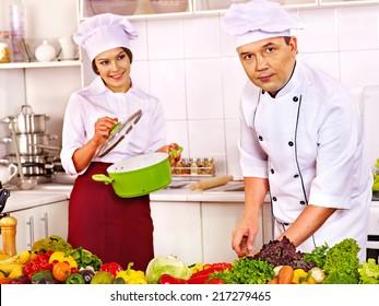Happy man in chef hat cooking chicken.