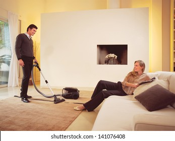 happy man cleaning the carpets in house an woman