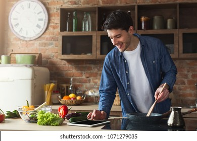 Happy man cooking healthy food with recipe, looking on digital tablet in the loft kitchen at home on sunny day. Preparing vegetable salad.
