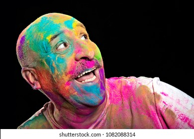 Happy man covered in brightly colored powder to celebrate the Indian Holi Festival looking to the side laughing in a head and shoulders portrait over black with copy space