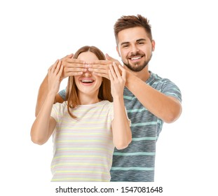 Happy man covering eyes of his girlfriend on white background