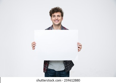 Happy man with curly hair holding blank billboard
