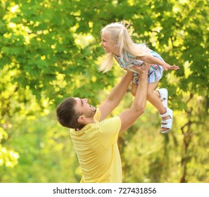 Happy man with daughter in park on sunny day