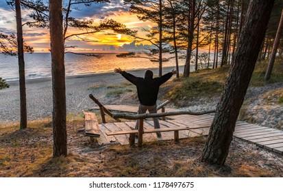 Happy man at dawn among pine forest near a shore of the Baltic Sea, Jurmala, Latvia
