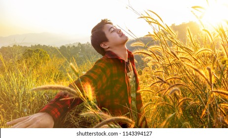 Happy man deep breathing fresh air on mountain, A man standing in beautiful valley, Great view on mountain, Relaxing man with beautiful sunshine on the mountain, Golden grass flower on mountain