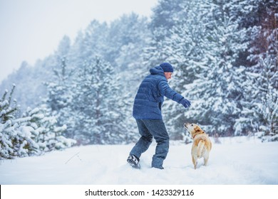 Happy man with dog play in snowy forest in winter