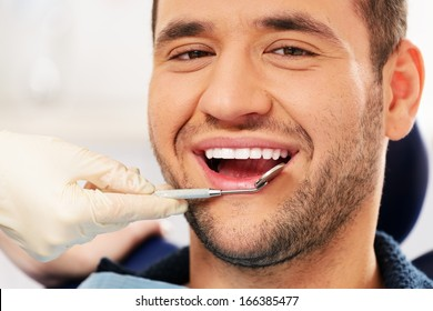 Happy man doing teeth checkup at dentist's surgery