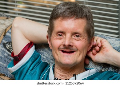 A happy man with Down Syndrome leans back on a couch with a big smile.  He is older, and has lost all his teeth.  He is looking at the camera and has several pens attached to his shirt.