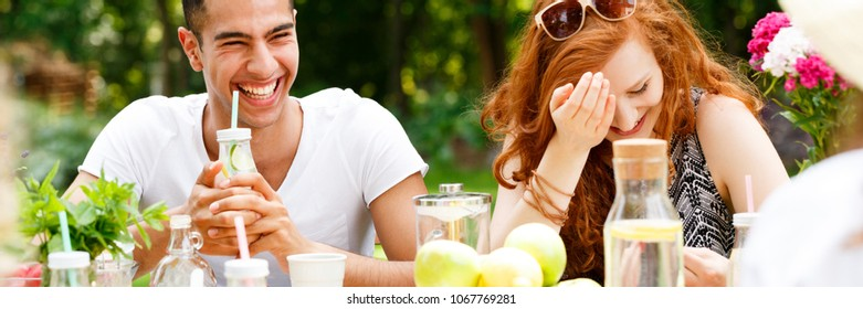 Happy man drinking water during a meeting with his girlfriend on the terrace