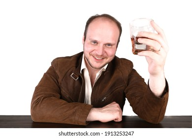 Happy man drinking whiskey standing at the bar counter. Guy wears brown leather jacket and white shirt. Isolated, white background.