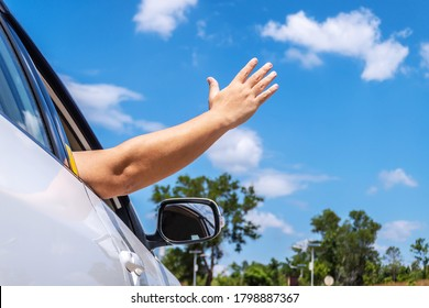 Happy man driver feeling the wind through his hands while driving in the countryside, freedom concept, copy space