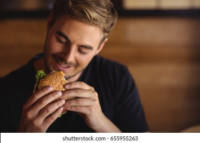 Happy man eating burger in restaurant