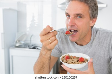 Happy man eating cereal for breakfast in kitchen looking at camera