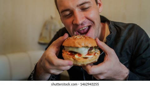 Happy man is eating fast food, hamburger. A man is sitting at the table and eating a cheeseburger