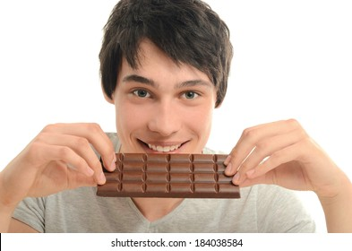 Happy man eating a yummy chocolate and having some sugar for an active day