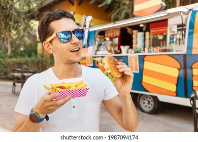 Happy man eats a burger and french fries near an outdoor food truck cafe. Streetfood and junk food concept