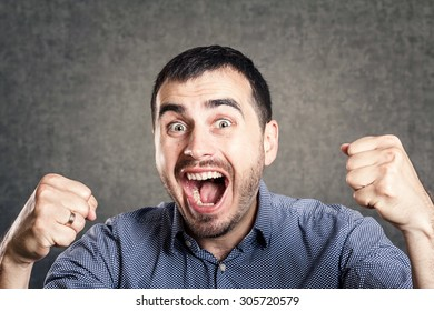 happy man exults pumping fists celebrates success