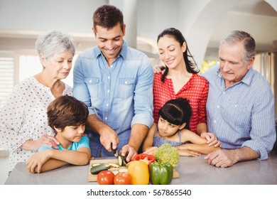 Happy man with family by kitchen table at home