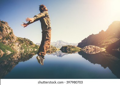 Happy Man Flying levitation jumping with lake and mountains on background Lifestyle Travel emotions concept outdoor