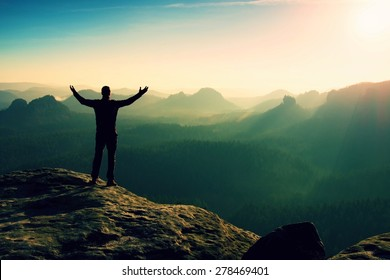 Happy man gesture of triumph with hands in the air. Funny hiker on the peak of sandstone rock in national park Saxony Switzerland watching into camera