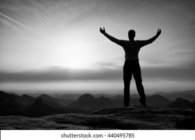 Happy man gesture of triumph with rams in  air. Funny hiker on peak of sandstone rock in national park Saxony Switzerland watching to horizon