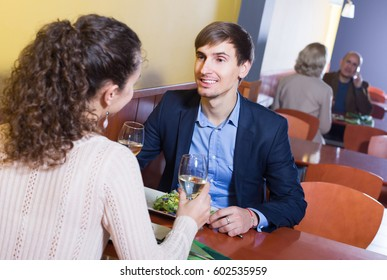 Happy man and girlfriend chatting as having date in restaurant