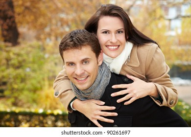 Happy man giving attractive woman piggyback ride in fall