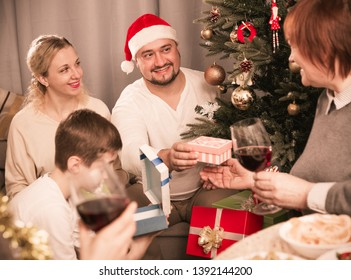 Happy man giving Christmas presents to family during dinner at home