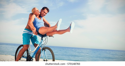 Happy man giving girlfriend a lift on his crossbar of bike on the beach