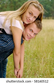 Happy man giving piggyback ride to woman outdoors
