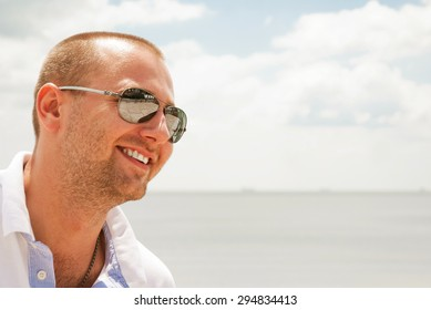 Happy man in glasses against blue sky in sunny day