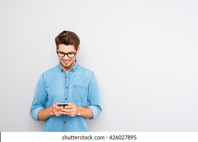 Happy man in glasses typing sms on gray background
