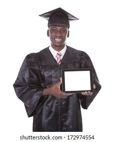 Happy Man In Graduation Robe Holding Empty Blank Tablet Pc Over White Background