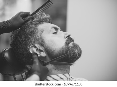 Happy man. Haircut of bearded man, archaism. Barber and hairdresser, future. Fashion and beauty, innovation. Man cut long beard and mustache with scissors. Hipster with serious face in barbershop, new